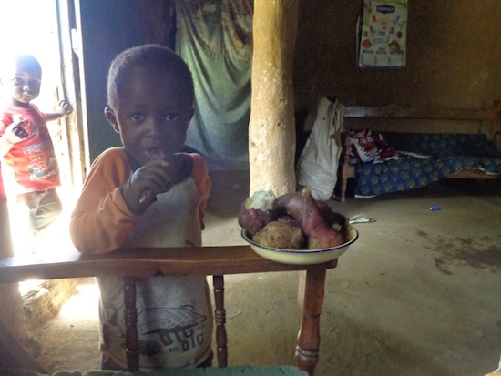 A Child eating a plate of Sweet Potatoes
