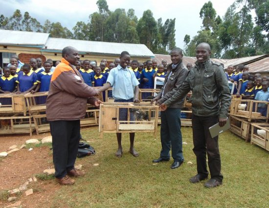 MakiniJames_One Hen Campaign Project Co-founders (in Leather Jackets) presenting a hen in a coop to pupil looking on is livestock officer from Kisii County Government